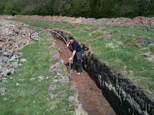 Ashley in a trench laying a ground loop collector pipe