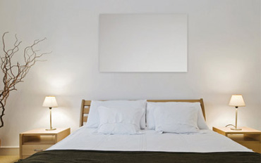 An infrared panel mounted on a bedroom wall